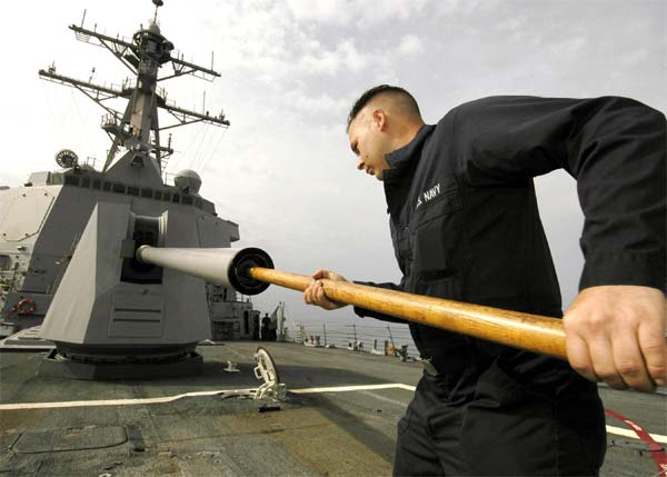 Gunner's Mate 2nd Class Michael West cleans the barrel of an MK-45 5-inch/54-caliber gun on the foc'sle of the Arleigh Burke-class guided missile destroyer USS Shoup (DDG 86). Shoup is currently underway in the Western Pacific operating area.