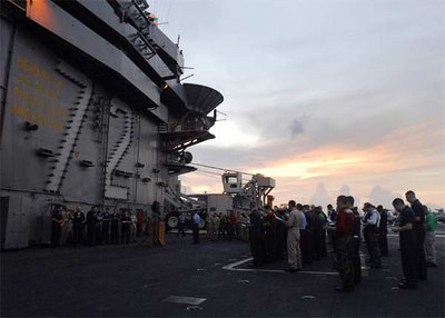 Sailors participate in a Easter sunrise service held on the flight deck aboard the Nimitz-class aircraft carrier USS Abraham Lincoln (CVN 72).