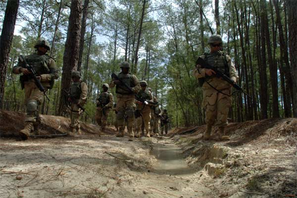 Sailors patrol through the woods during a simulated Improvised Explosive Device (IED) awareness exercise as part of the Navy's Individual Augmentee Combat Training course at Fort Jackson, S.C.
