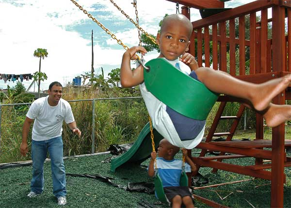 Aviation Machinist's Mate 2nd Class Augusto Baez assigned to Helicopter Anti-Submarine Squadron Seven (HS-7) plays with two local children on a swing set at the Prince William Alexander School for Special Needs Day Care playground.