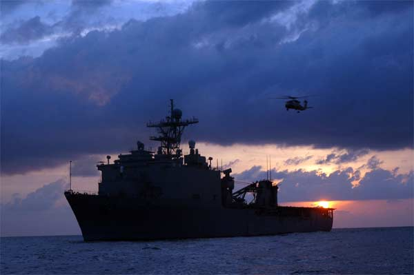 An SH-60B conducts an early morning fly-by of the amphibious dock landing ship USS Oak Hill (LSD 51).