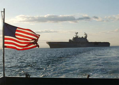 The American flag flies high as the Utility Landing Craft (LCU-1635) travels to unload excess ammunition off of the amphibious assault ship USS Tarawa (LHA 1).