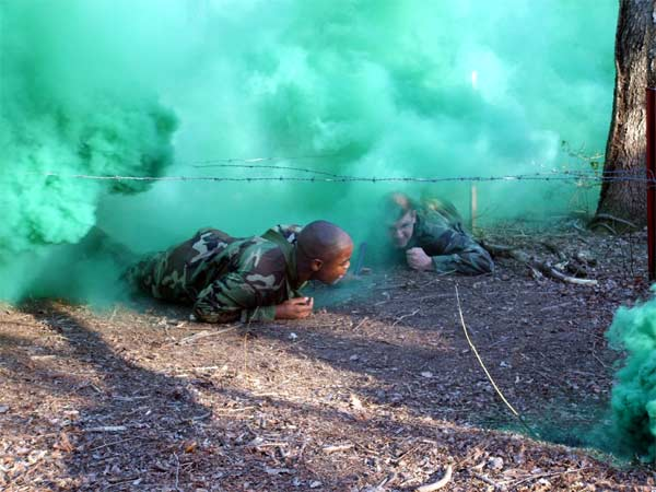 U.S. Navy Master-at-Arms 2nd Class Warrne Summers and Air Force Airman 1st Class Andrew Prunitis, both students in the Air Force Phoenix Raven Class 06-D here, crawl through smoke pulling a patient under wire during combat first aid training.