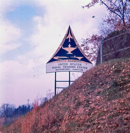 """USNTC BAINBRIDGE - """"Trained Manpower Makes Seapower"""".  1964 sign at entrance to USNTC BAINBRIDGE."""
