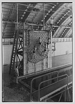 USNTC Bainbridge - Drill Hall and Swimming Pool - Net Drill - April 28, 1943.<br /> <br /> During my Boot Training in 1955, I remember something like the Net Drill, plus a 20 foot jump, simulating holding onto a kapok life preserver with your right arm crossed over to your left shoulder, and with your left hand holding your nose as you jumped from the platform.  I was not terrified, but I did have to muster up the courage to climb the ladder to the platform to make the jump!  The depth of the pool under the platform was approximately 8 or 9 feet deep.<br /> <br /> When I joined the U.S. Navy I was a non-swimmer, but with the help of our Company Commander, Michael J. Brigande, I learned pretty quickly.  I failed the first attempt to swim around the four sides of the pool without touching the bottom of the pool.  On my second attempt I actually made it with my Company Commander walking the edge of the swimming pool urging me onto the finish.