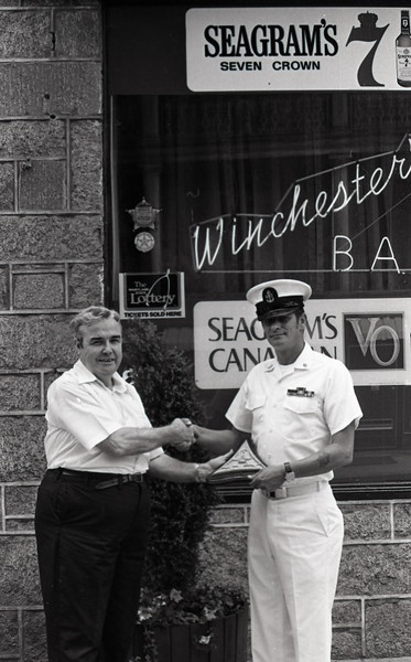 "John Malloy, the owner of the Winchester Hotel is presenting ""Chief Ski"" (Chief Petty Officer Stephen Kowalski) with a plaque commemorating the ""last detail."""