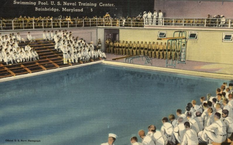 USNTC BAINBRIDGE, MD Swimming Pool.  Possibly this may be a swimming meet!<br /> <br /> What I remember also about the Swimming Test . . . As a Company we went to the Swimming Pool with bathing suits (brief style as in the photo) which were itchy to wear, I believe they were made of the same fabric as the stocking caps we were provided.  <br /> <br /> We all stripped, showered and then proceeded naked to the swimming pool with our bathing suits in one hand and holding our 'peckers' in the other.  We had to present ourselves to the Master Chief who ran the swimming pool and he inspected us as we 'skinned back' the foreskin.  He sent back several to re-shower and then be reinspected.  <br /> <br /> I remember one sailor he chewed out for having not done a thourgh job of cleaning himself and made him an object for all of us to see as what not to have under our foreskin!  He shouted back to the sailor 'go back and scrub it clean with a brush (OUCH!) and come back to me for inspection'!<br /> <br /> When I joined the U.S. Navy I was a non-swimmer, but with the help of our Company Commander, Michael J. Brigande, I learned pretty quickly. I failed the first attempt to swim around the four sides of the pool without touching the bottom of the pool. On my second attempt I actually made it with my Company Commander walking the edge of the swimming pool urging me onto the finish.