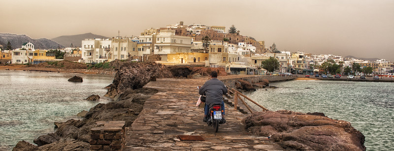 Moped on his way from the port to the old town of Naxos, Greece