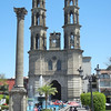 A Peace Column In Front Of A Large Fountain And The Catedral