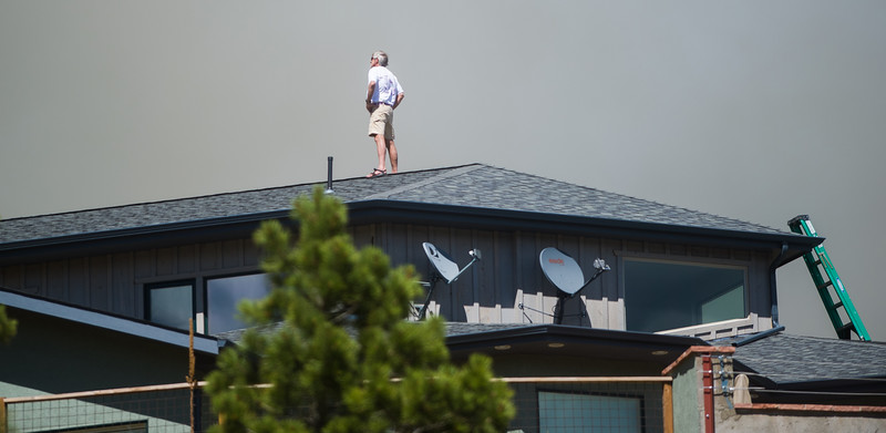 "A man watches a fire near Nederland from the roof of his house on Hurricane Hill Saturday. <br /> More photos:  <a href=""http://www.dailycamera.com"">http://www.dailycamera.com</a><br /> (Autumn Parry/Staff Photographer)<br /> July 9, 2016"