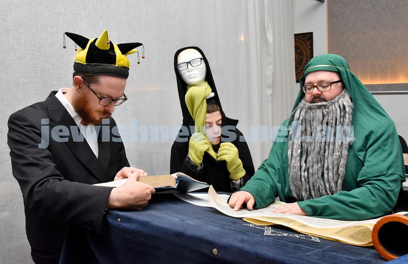 Purim at Nefesh Synagogue. Rabbi Chanoch Sufrin (right) reads the Megilah as Rabbi Aron Moss (left) and Aron Sufrin follow. Pic Noel Kessel