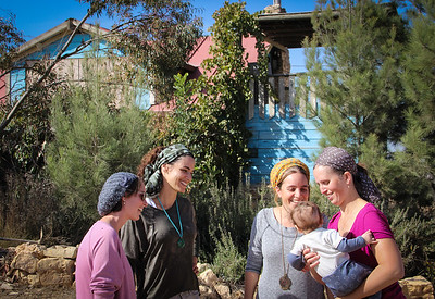Shahar Aharonovitch (right), with her 3-month-old, stands in front of her house surrounded by friends and neighbors. Shahar's husband, Zvi, is away doing reserve duty, while their carpentry business next door is under threat to be destroyed any day. They have five other children, up to age 13. Their house is on the list for destruction as well.