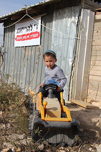 Sign behind the child says, 'No more destruction; normalize Netiv Avot.'