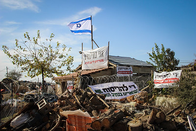 "The carpentry workshop, owned by Zvi Aharonovitch, stands at risk of imminent destruction. The sign below the flag says, ""I am in reserves; and they're destroying my house."""