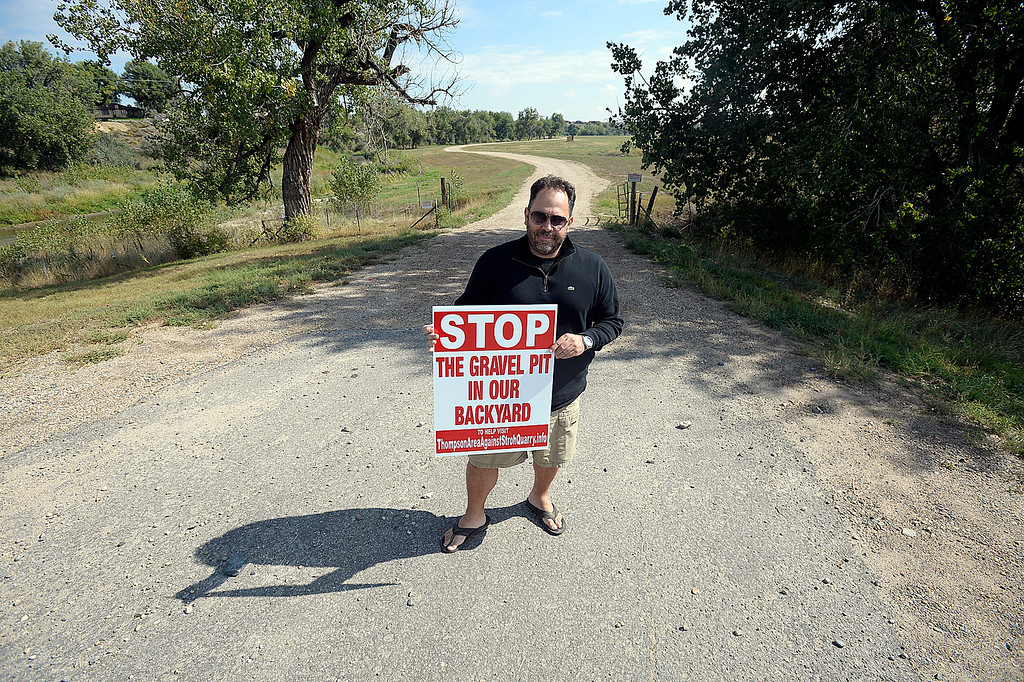 . Victor Betelli poses for a photo holding a sign Tuesday, Sept. 25, 2017, near a proposed gravel pit between his neighborhood, Thompson Crossing and Thompson River Ranch to the south in Johnstown.    (Photo by Jenny Sparks/Loveland Reporter-Herald)