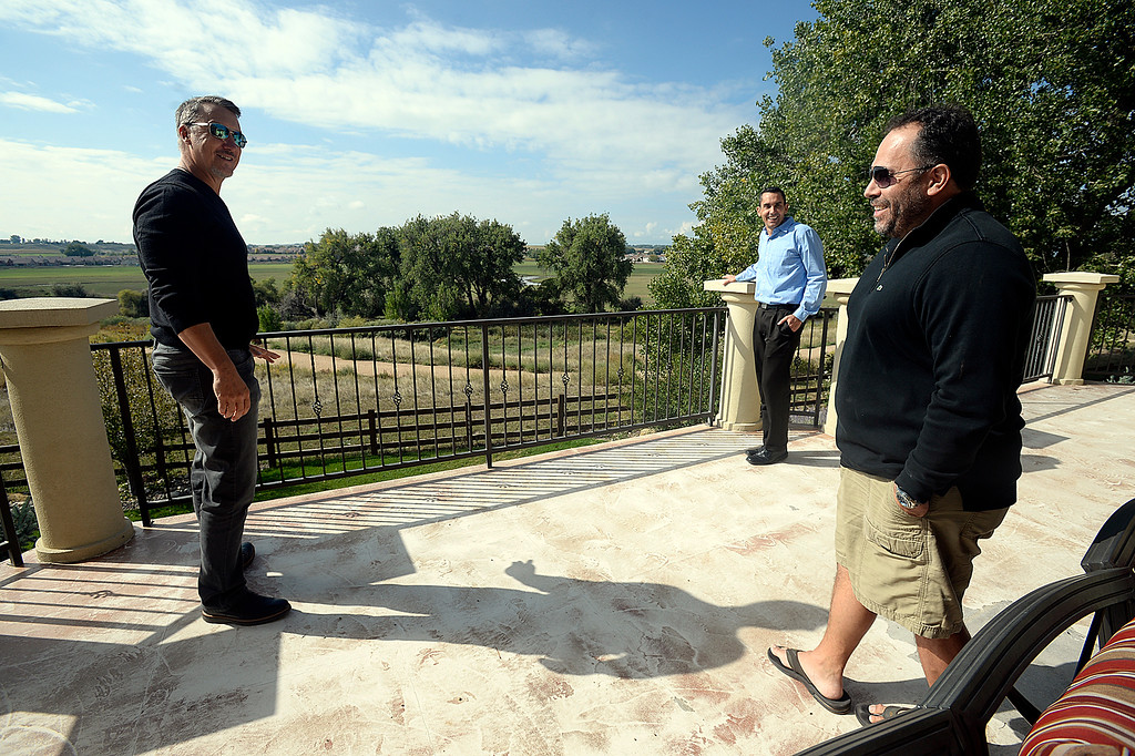 . Thompson Crossing residents Jason Johnston, left, and Victor Betelli, right, and Thompson River Ranch resident Kevin Lemasters, center right stand on Btelli\'s patio Tuesday, Sept. 25, 2017, overlooking an area where a gravel pit is proposed in Johnstown.    (Photo by Jenny Sparks/Loveland Reporter-Herald)
