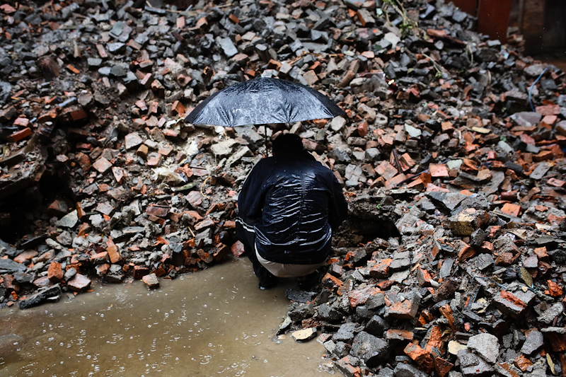 A man crouches next to a pile of rubble in a downpour in Bhaktapur Durbar Square in Kathmandu, Nepal, April 28, 2015. (Photo by Mallory Olenius)