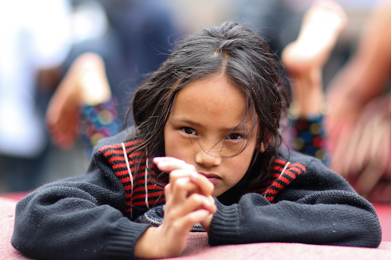 In Kathmandu, a young girl looks up in one of the 'tent cities' built in place of lost homes following the devastating earthquake.  Photo by Mallory Olenius