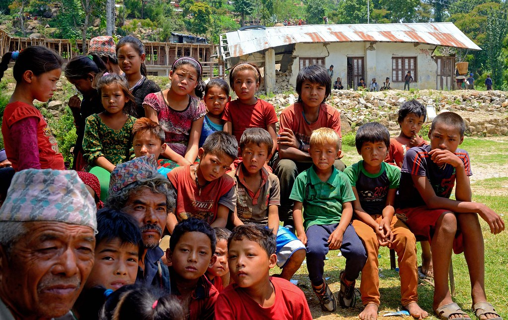 Children sit in front of their damaged school building listening to aid workers promising them galvanised iron sheets for temporary shelter during the coming monsoon months