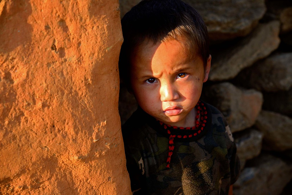 A child gazes at the photographer from the walls of his home which is all that  is remaining.