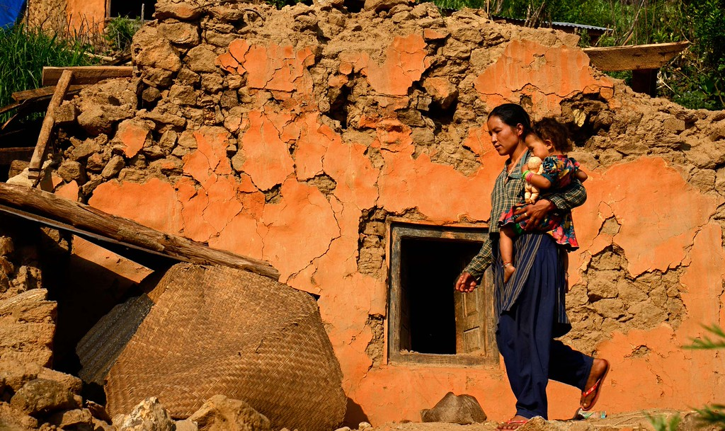 A mother and daughter walk  past their  shattered home to collect relief materials from the school below