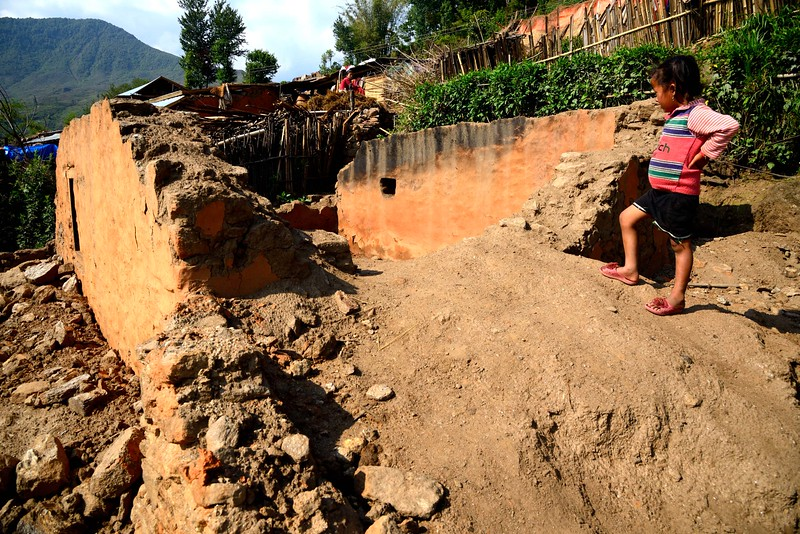Six year old Maya stands beside  the ruins of her old home...
