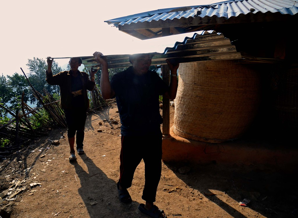 Two villagers carry the galvanised iron sheets received from the  relief workers - but it is not enough to build a shelter.