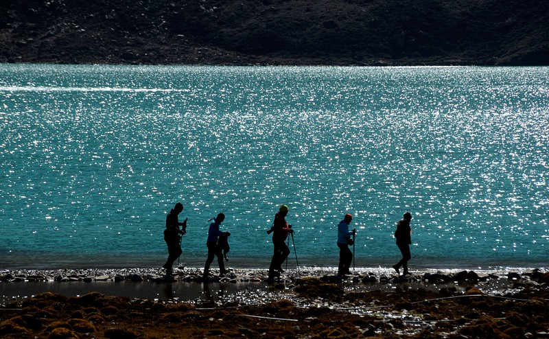 Trekkers walk past the third  lake of Gokyo on their climb to Gokyo Ri