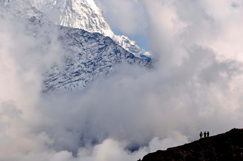 Clouds clear after a snowstorm at Luza revealing the serrated ridge of Thamserku
