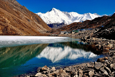Cho Oyu and the partially frozen third lake of Gokyo. To the left is the steep trail to Gokyo Ri while the valley ahead leads to the fifth lake of Gokyo and the Cho Oyu Base Camp beyond