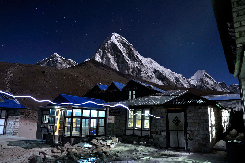 The lodges of Gorak Shep. In the background is Pumori and Lingtren and the trail to Kala Pattar. The white line is a  trekker's headlamp going into the lodge.