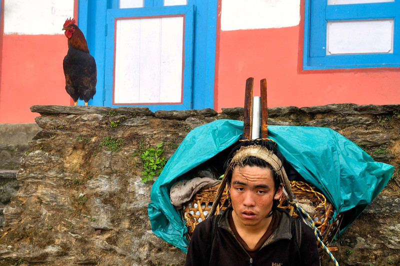 An exhausted Prakash rests his load before a house on the long trail down from Lukla to Salleri