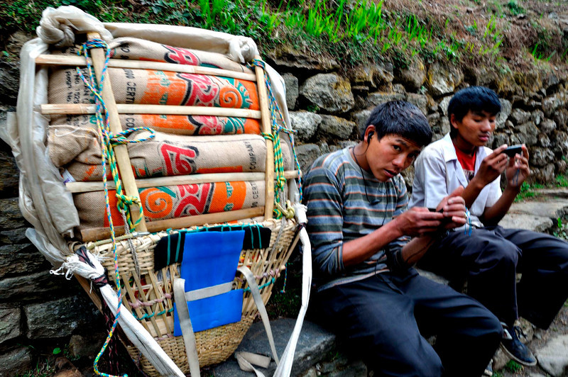 Checking their messages on the cell phones. Communication has now come to the Khumbu and most porters have cell phones.