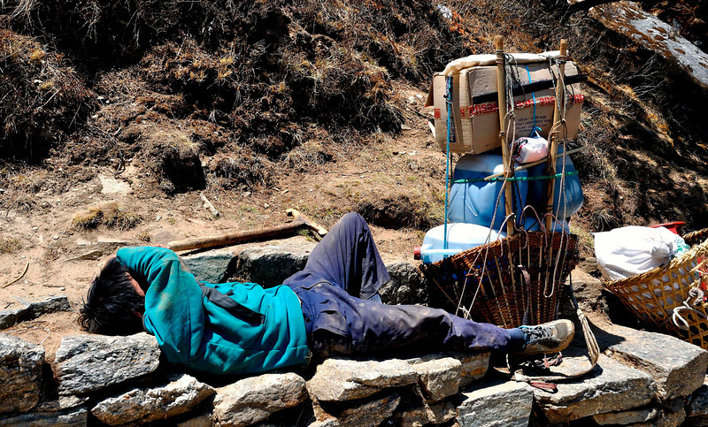 Exhausted in the summer sunshine, a porter rests before the climb to Mongla on the route to Gokyo. His load includes kerosene for the lodges up the trail.