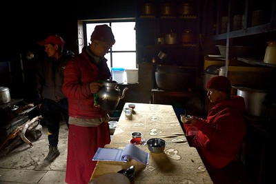 The kitchen of Mu Gompa where a lama is served a cup of salted butter tea