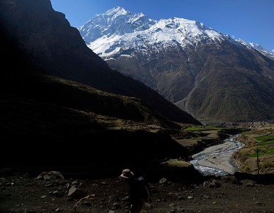 A trekker heads towards Mu Gompa high above the twin villagesof Nyile and Chule seen in the valley below