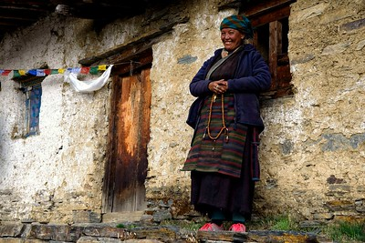 A nun at the entrance of Dhepudoma nunnery at 4000 metres situated on the edge of a cliff higher than Mu Gompa
