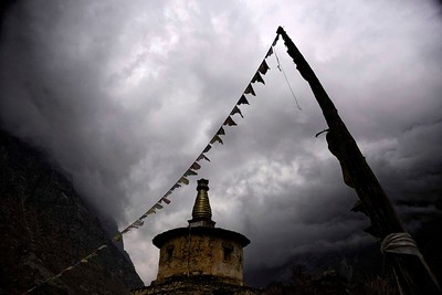 An afternoon thunderstorm approaches near the village of Chule where this large chorten stands before the village entrance