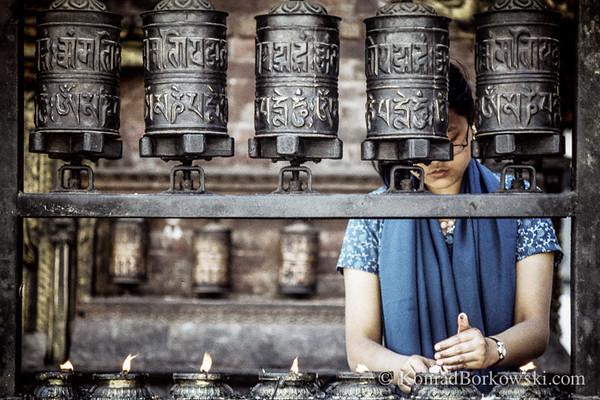 Nepali woman and the prayer wheels, Kathandu, Nepal