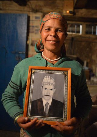 Ama Tileu with of photgraph of her late husband. Note that she now wears green coloured clothes to indicate being a widow.