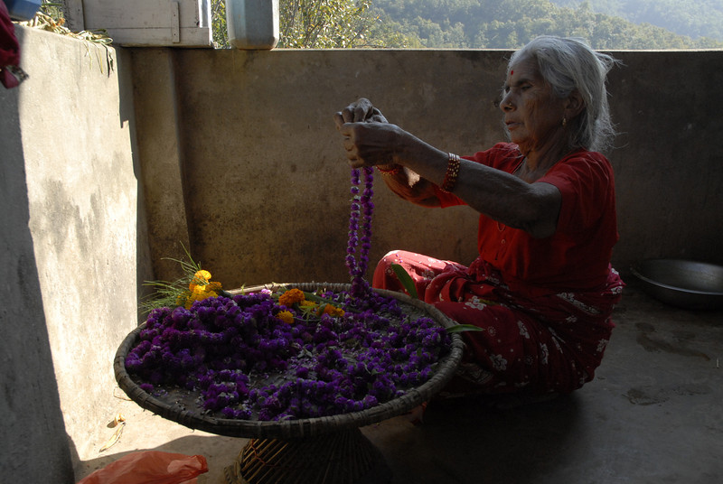 Sahadev's aunt who had traveled from Chitwan to honor her brother duringTihar. She is making our garlands.