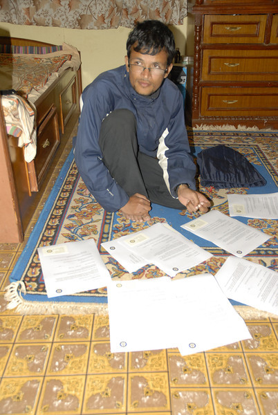 Sahadev looking over the school agreements to be signed.