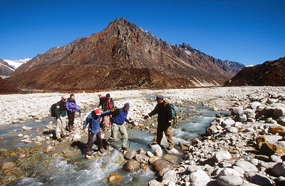 Trekkers crossing a stream in the Ghunsa Khola valley, near Kambachen, on their way to Jannu Base Camp.