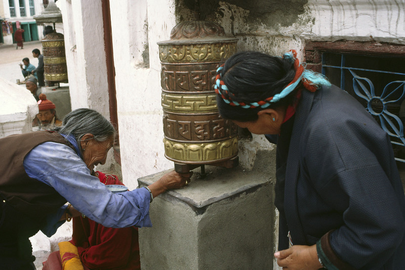Tibetan women at a prayer wheel.
