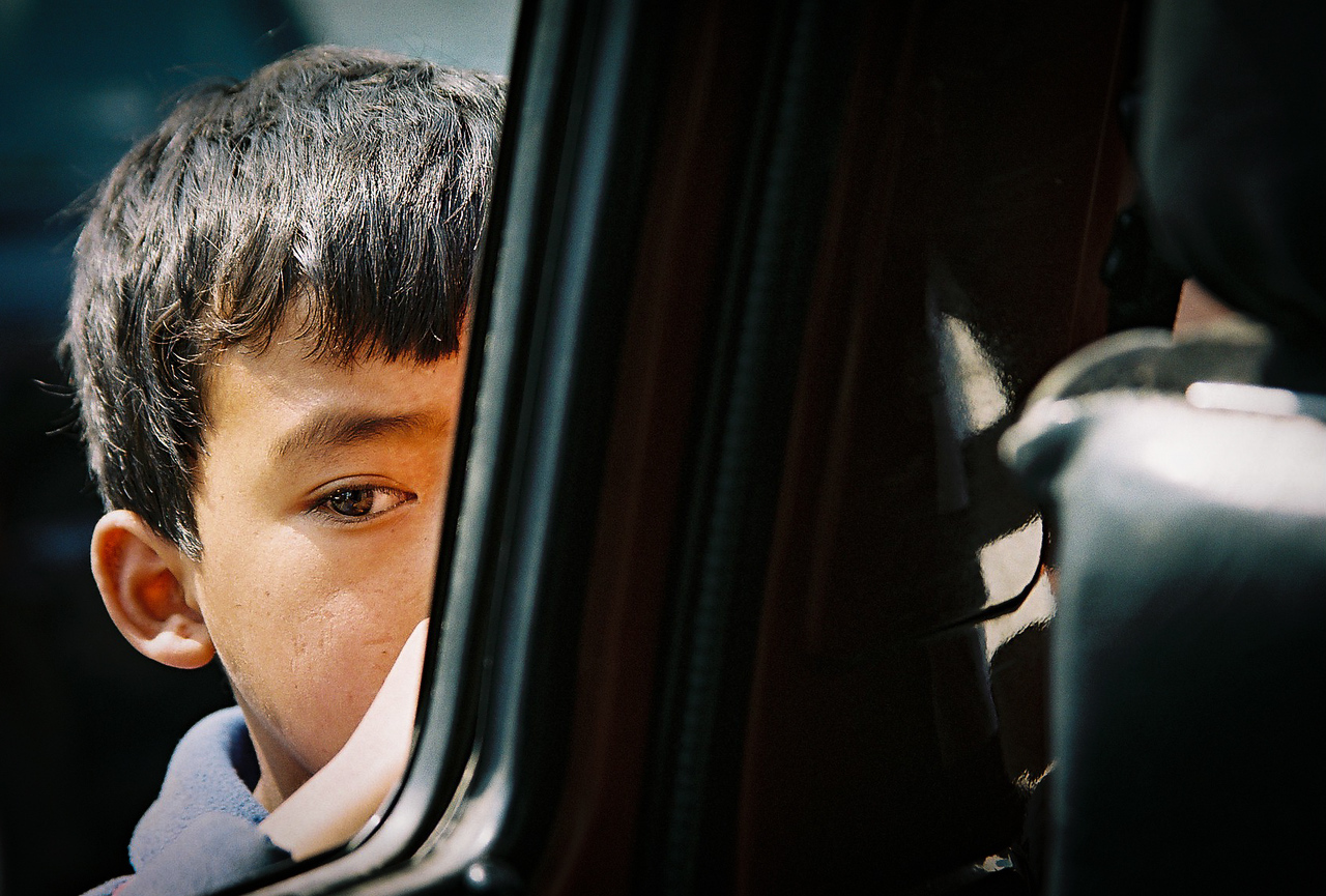 Boy selling Nepali newspapers through the taxi window