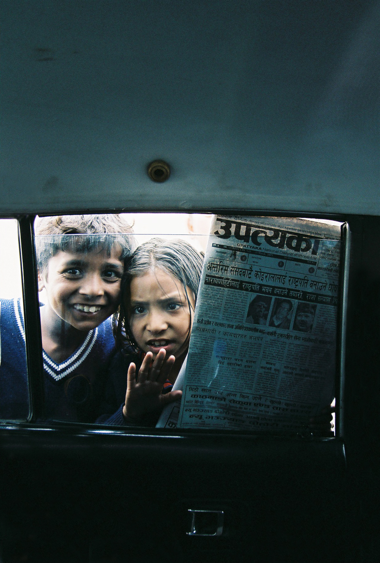 Children selling Nepali newspapers through the taxi window