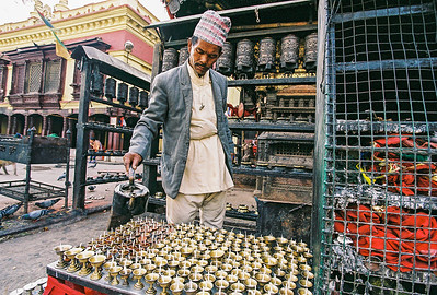 Man filling the butter lamps at the Swayambhunath Stupa