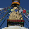 The solid whitewashed dome of the stupa symbolizes the womb or creation. It is surmounted by wooden pillar surrounded by a gilded cube (the phallic complement to the female dome). The eyes painted on each side of the cube are the all-seeing primordial Buddha (Adi-Buddha). The 'nose' represents light  which unifies all things. The spire of gold disks stacked above the cube represent the 13 steps to enlightenment. The umbrella like object at the top represents the attainment of enlightenment.