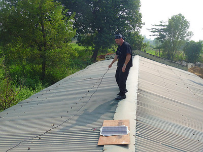 Marc Kaman on the roof with the panels.   (photo by Gibbs Yim)