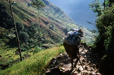 """Kenja (5,380 ft).  Porter descending rocky trail.  This particular porter is known as a """"trucker"""" porter.  He was carrying nearly 200 pounds of beer and kerosene to Namche."""